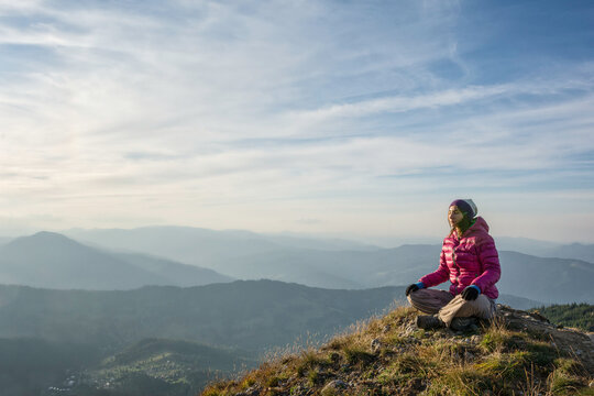 Young woman meditating on a mountain peak