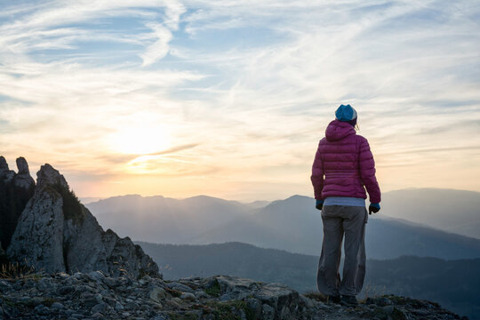 Young woman watching a beautiful sunset from a mountain peak