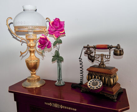 Vintage telephone on the hall table with a lamp and pink flowers
