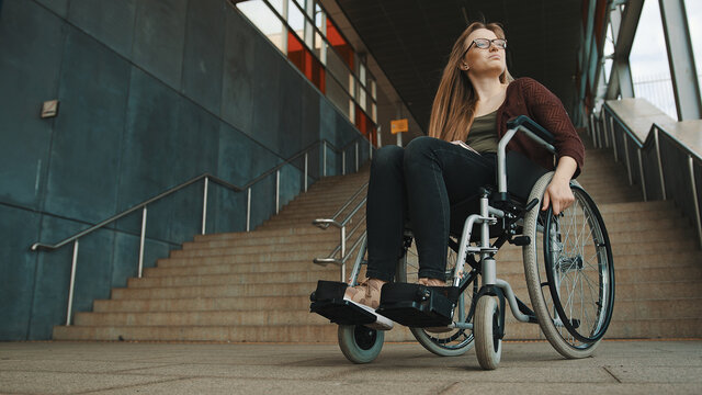 Young discouraged caucasian woman in the wheelchair in front of the staircase looking around for accessible way. High quality photo