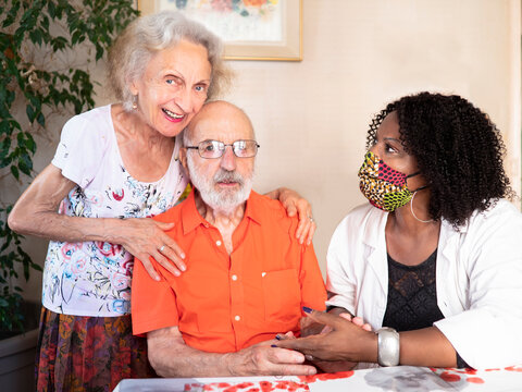 African American medical assistant helping an ederly couple at home in times of Covid19 pandemic