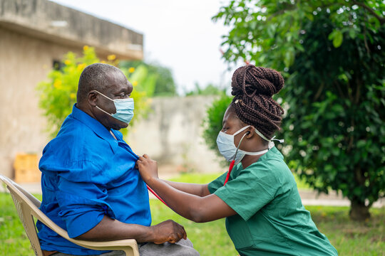 image of an aged African man being checking up by a health worker-young black nurse wearing a face mask taking care of an old man- health worker at home service