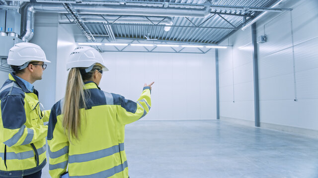 Two Engineers Talking, Standing in the Middle of an Empty Warehouse, Inspecting, Planning Future Factory Layout. Professionals Industrial Designers Strategizing about New Manufacturing Plant Design.