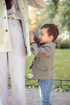 Little boy walks with his mom in autumn park