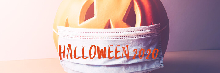 Halloween 2020 text. New Normal and New reality concept. Orange Pumpkin or Halloween Jack o Lantern in medical protective mask, halloween and covid-19 concept, banner size