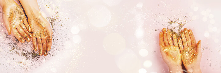 Beautiful womans hands covered in golden glitter on pink background, banner size with copy space