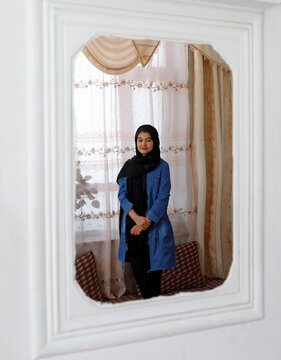 Shamsia Alizada,18, who has come top in the country's university entrance exam, is reflected in a mirror after an interview at her house in Kabul