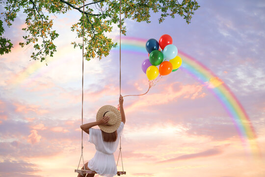 Dream world. Young woman with bright balloons swinging, rainbow in sunset sky on background