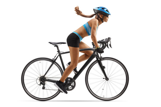 Full length profile shot of a woman in sportswear riding a bicycle with a helmet