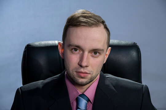 Portrait of a young businessman about 30 years old in a suit sitting in an office in a leather chair, looking at the camera. Concept: novice and successful politician, competitor in small business,