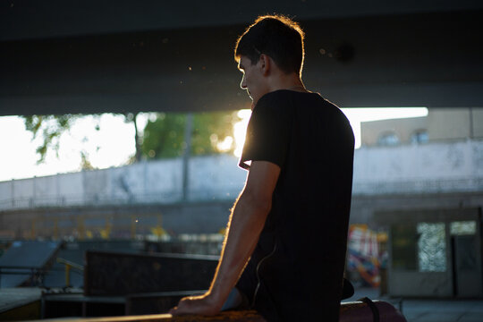 photo of a guy in a black T-shirt with backlight against a skatepark