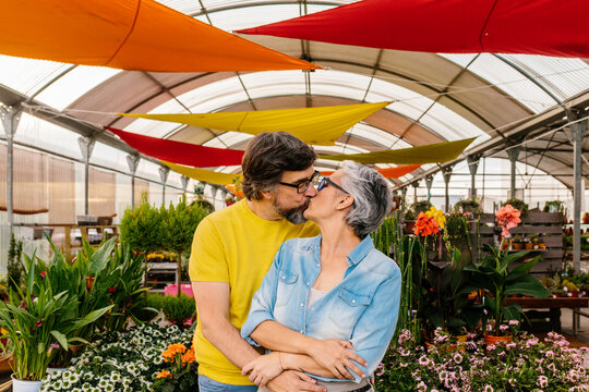 Happy mid adult couple posing in their nursery small business