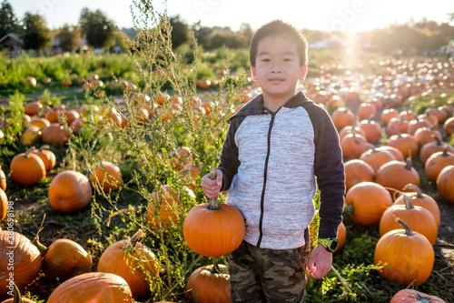 Asian Boy Holding a Pumpkin