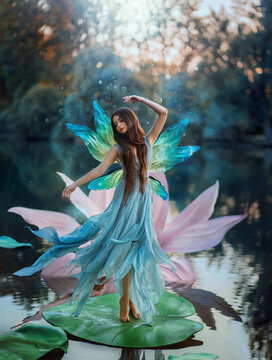 Beautiful young fantasy woman in the image of a river fairy dances on a water lily flower. A long silk dress flies in the wind, butterfly wings glisten. Background evening dark nature, blue lake.