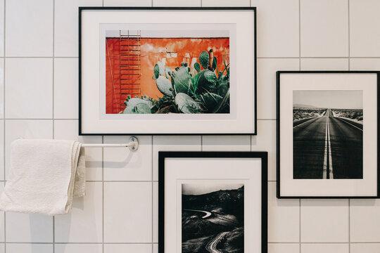 White Tiled Bathroom Detail With Framed Photographs