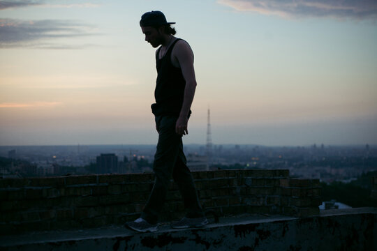 silhouette of a guy against the background of the night city and sky