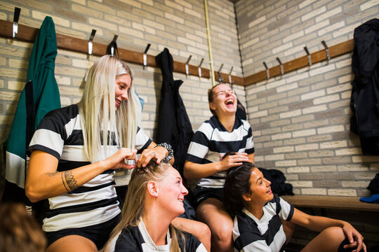 Two female rugby players getting their hair in braids by their t
