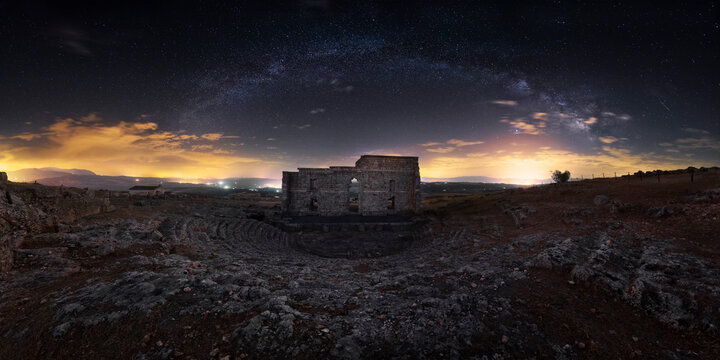 Wide angle ancient Roman theater of Acinipo city in remote landscape with colorful sunset sky on background