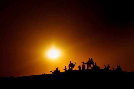 Silhouettes of camel caravan with people walking in dark desert against sunset sky with bright sun shining over horizon in India
