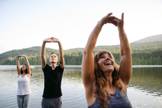 A group of people practicing yoga outside.