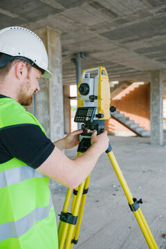 Surveyor engineer working at construction site with measuring eq