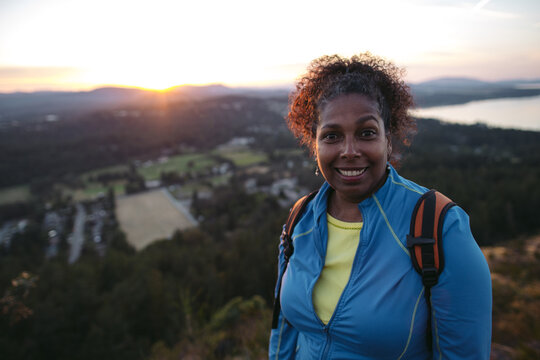 Portrait of middle age woman on mountain at sunset.