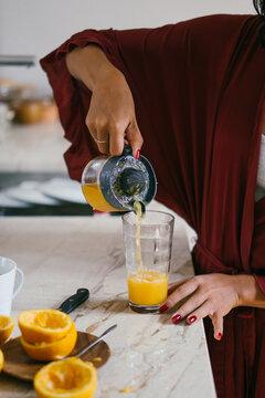 Woman preparing an orange juice indoor
