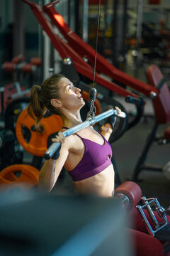 girl doing vertical block pull in the gym