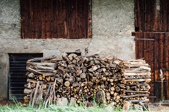 Wood stacked outside a rustic alpine barn.