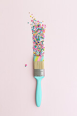 Paintbrush and colorful cake sprinkles