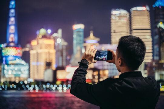 Man taking photos beside Huangpu River at ShangHai, China