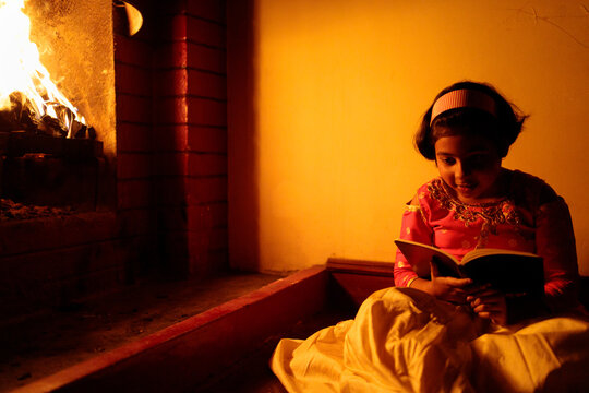 Little girl reading a book sitting by the fireplace