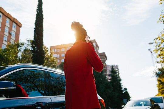 Back view of elegant woman browsing smartphone in road