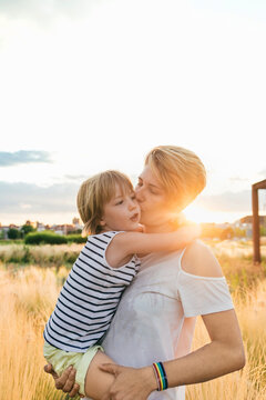 Mother holding her little girl during a beautiful sunset in the countryside