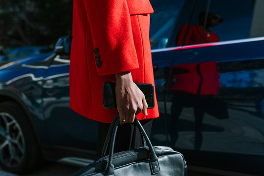 Stylish black woman with smartphone and bag opening car door in street