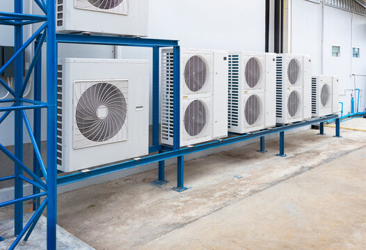Condenser unit or compressor outside industrial plant building. Unit of central air conditioner (AC) or heating ventilation air conditioning system (HVAC). Electric fan and refrigerant pump inside.