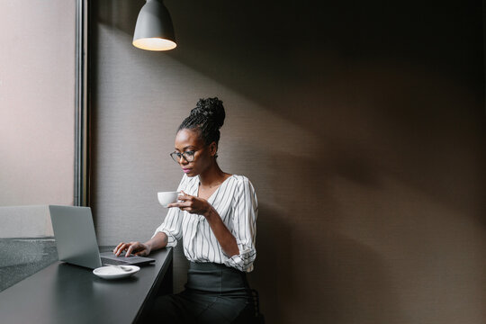 Cheerful woman drinking coffee and working on laptop at table