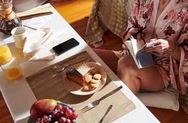 Crop woman reading during breakfast