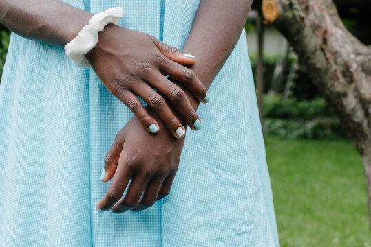 Black girl's hands on a light blue dress