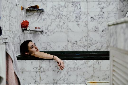 Sad girl lying in bathtub with cigarette