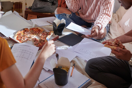 Crop students with pizza and noodles doing homework on bed