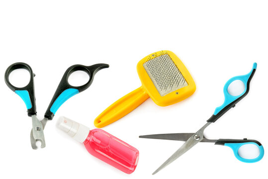 Scissors, clipper, shampoo and comb for dog grooming isolated on a white background.