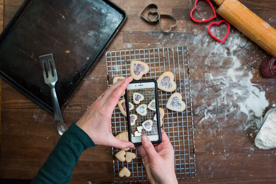 Woman's hands taking photos of Valentine's Day cookies