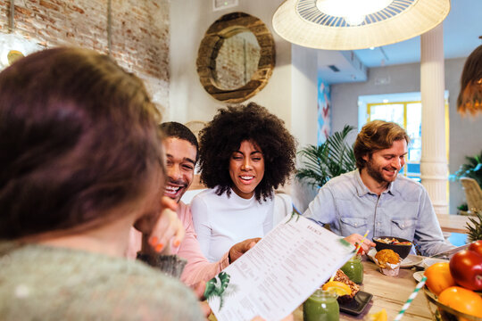 Cheerful friends reading menu in cafe