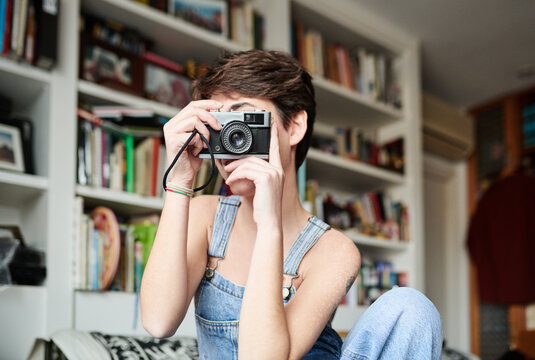 Cheerful female taking photos at home
