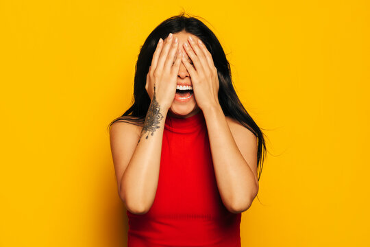 Gorgeous mixed race woman smiling over yellow background and covering face with hands