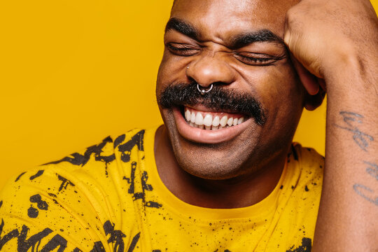 Happy african american man over yellow background