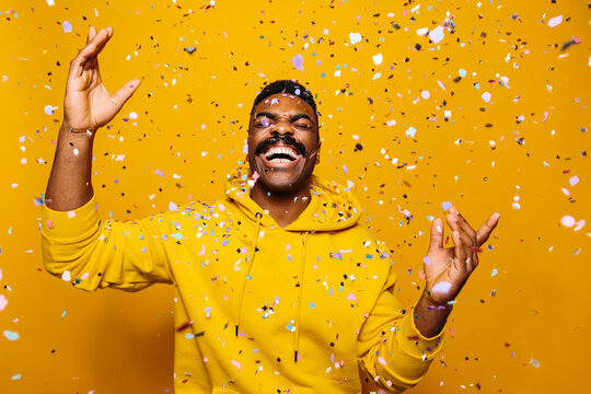 Happy african american man over yellow background with confetti falling on head
