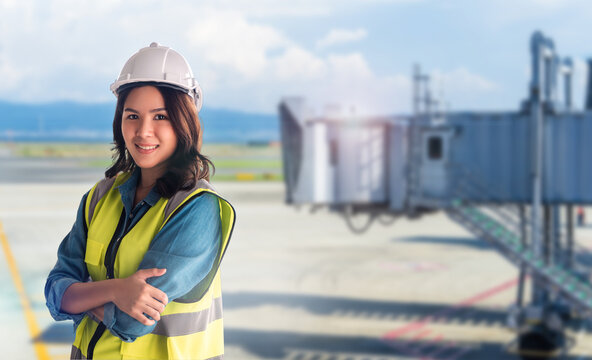 Aviation Confidence Female asian Engineer with safety equipment with Airport in the background.