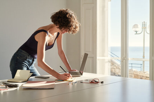 Calm slim woman taking notes in notepad while working on project at home